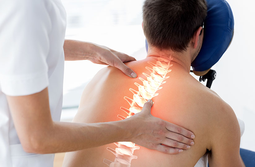 A physio presses their thumb into a patient's spinal area