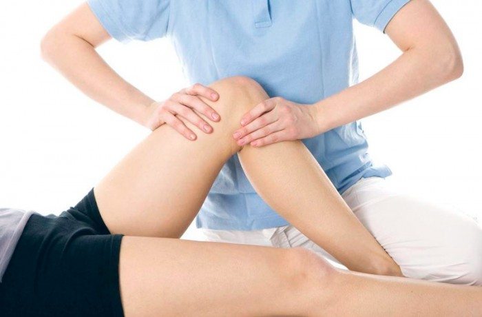 A physio massaging someone's knee area